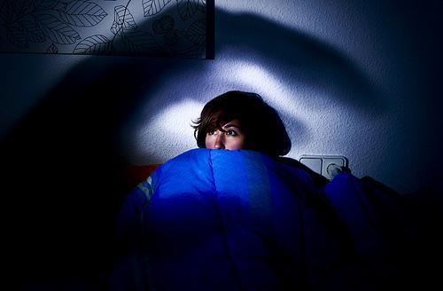 ベッドの中で怖がる女性