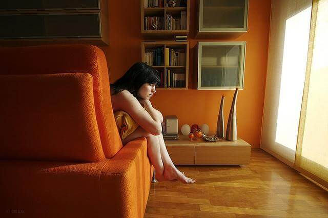 ソファでクッションを抱える女性