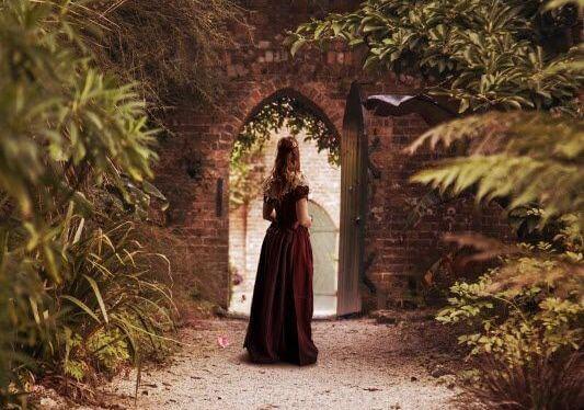 アーチ型のゲートの前に立つ女性