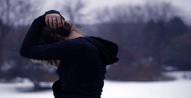 雪の中で頭を抱える女性