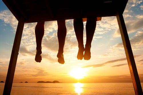 夕暮れの水辺に座る二人の足