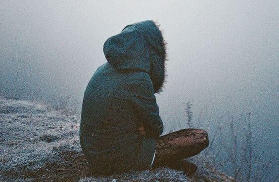 冬に一人で座るフードを被った人