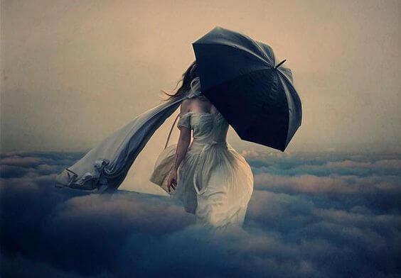 雲の中を歩く傘を差した女性