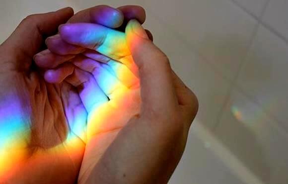 手の上の虹色の光