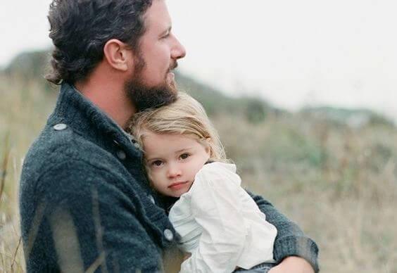 娘を抱く父親