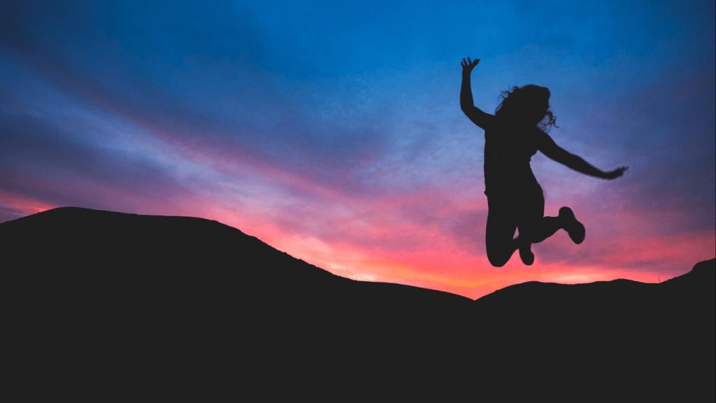 夕暮れの中ジャンプする女性