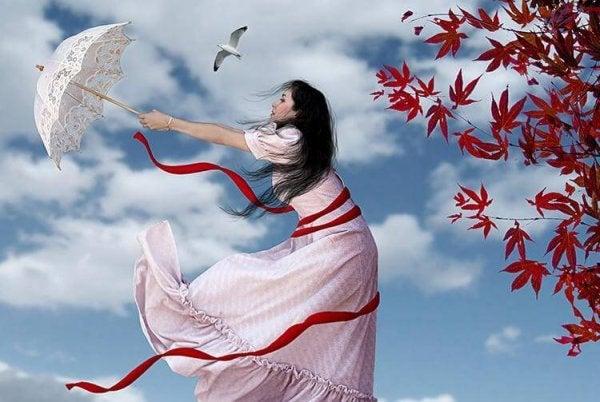 傘を持って風に吹かれる女性