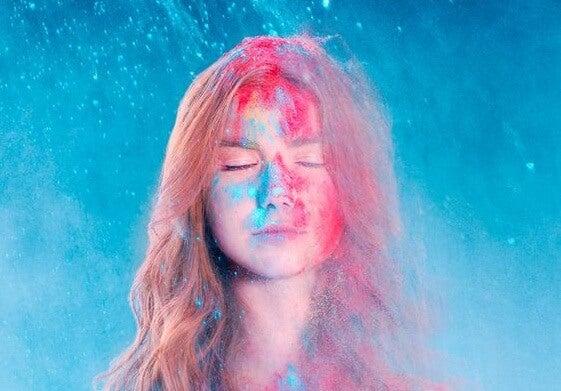 青い光の中で目を閉じる女性