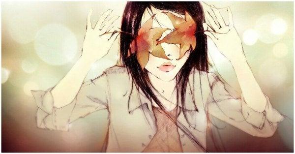 落ち葉で顔が覆われた女性