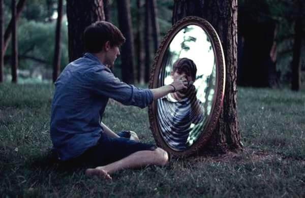 鏡の中に手を伸ばす少年