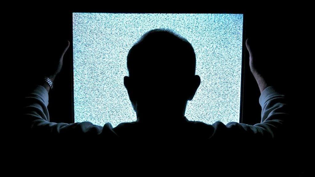 白黒のテレビ画面を見る男性
