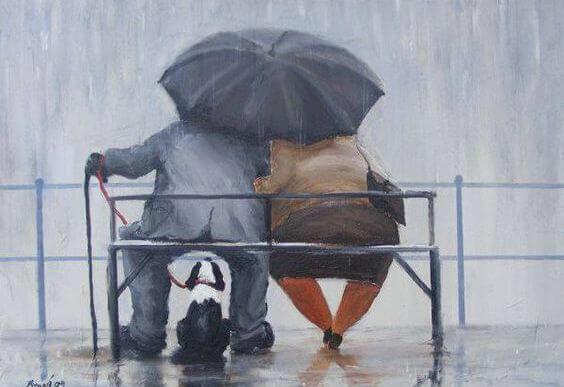 傘をさしてベンチに座る老夫婦