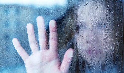 窓ガラスに手を当てる女性