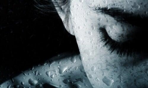 水滴のついたガラスの向こう側の女性