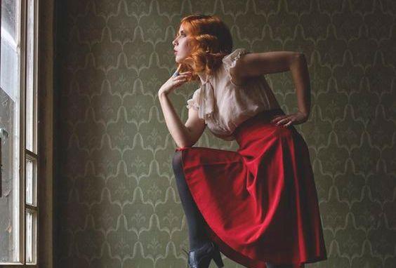 窓辺でポーズをとる赤いスカートの女性