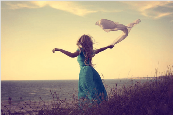 海辺の青いドレスの女性