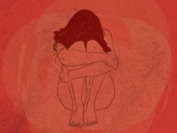 赤いうずくまる女性
