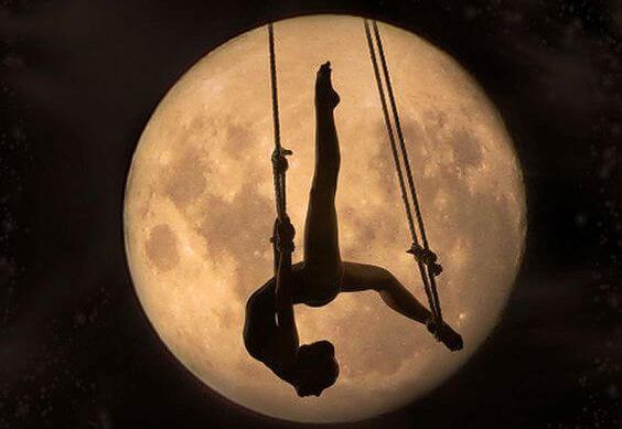 月とアクロバットをする女性