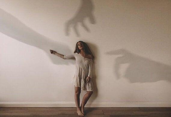 手の影に追われる女性