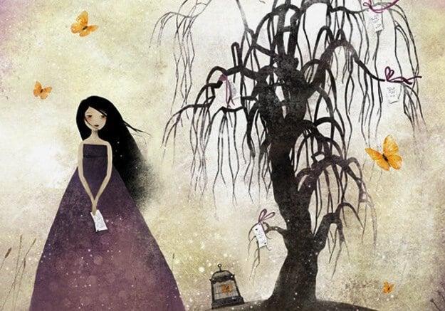 枯れ木の横に立つ女性