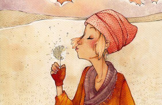 タンポポの綿毛を吹く女性