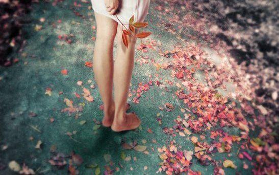 落ち葉を手にする裸足の女性