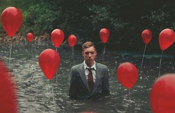 水の中に立つスーツの男性と赤い風船