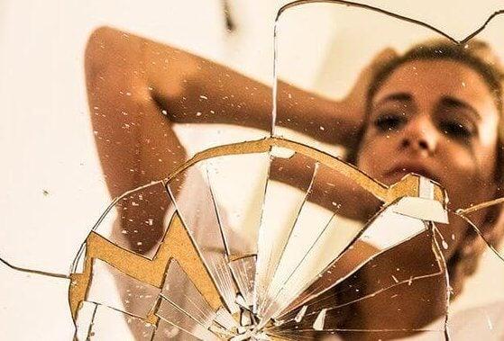 割れた鏡に映る泣く女性