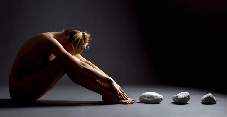 膝を抱える裸の女性
