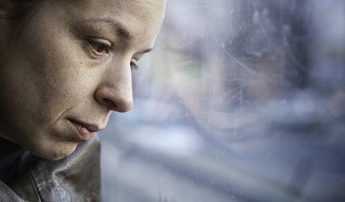 窓の外を悲しげに見る女性