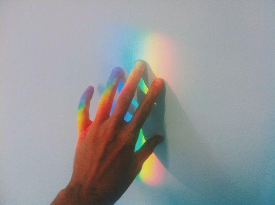 虹が映る壁に触れた手