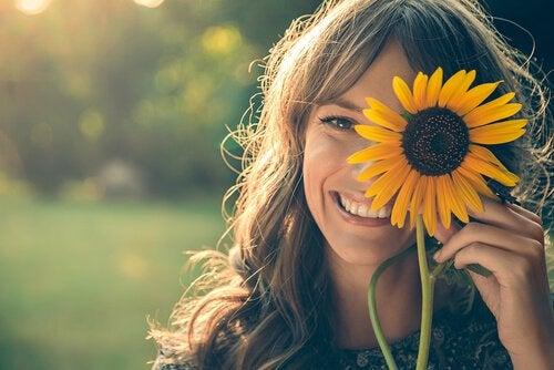 ヒマワリに顔を隠して笑う女性