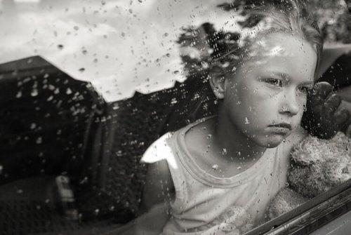 雨の日の外を眺める子供