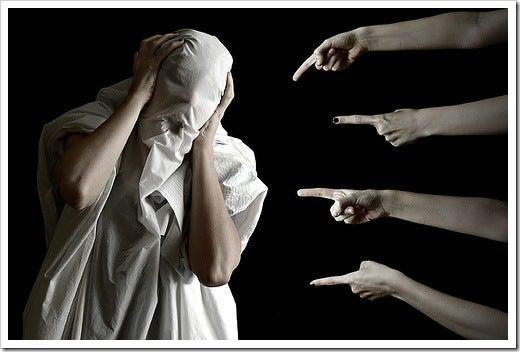 指をさされて顔を覆う人