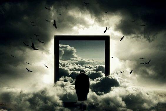 雲の上に立ちうなだれる男性