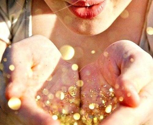 金粉を手から吹き飛ばす女性