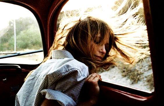 車の窓から頭をのぞかせる女性