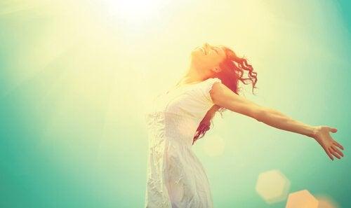 晴れの空に手を広げる女性
