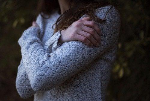 寒さに身をすくめる女性