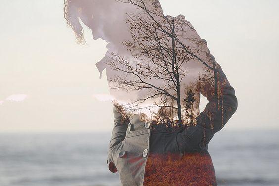 海辺を歩く女性の影に映る森