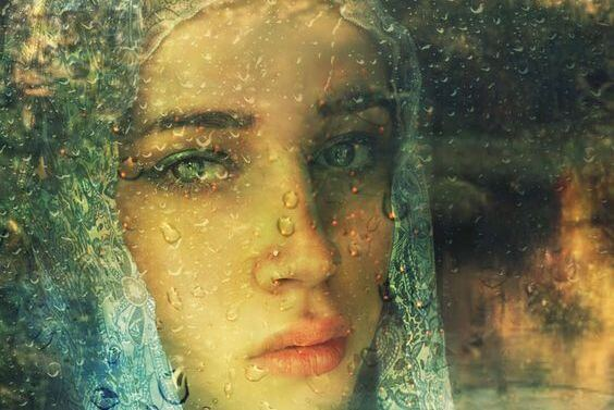 窓の外を眺めるベールをかけた女性