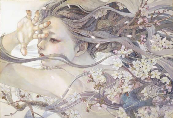 花に囲まれ風に吹かれる少女