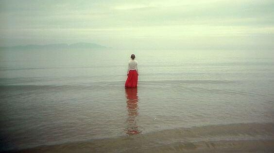 海辺に立つ赤いスカートの女性