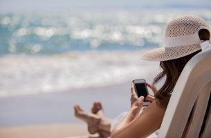 海辺でスマホを使う女性