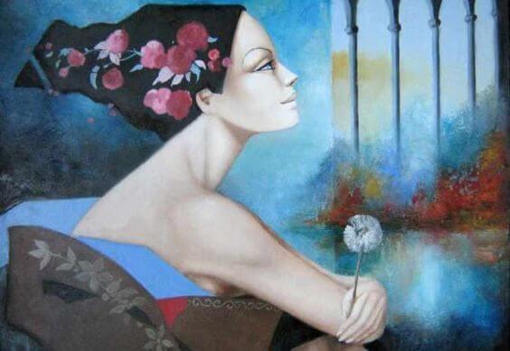 タンポポの綿毛を手に遠くを見つめる女性