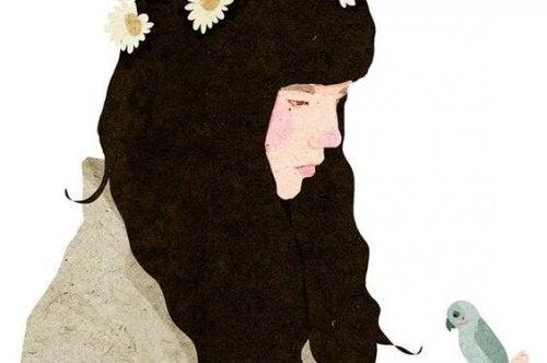 小鳥を見つめる黒髪の女性