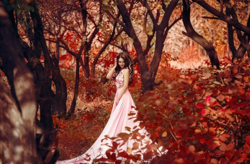 秋の森に立つドレスの女性