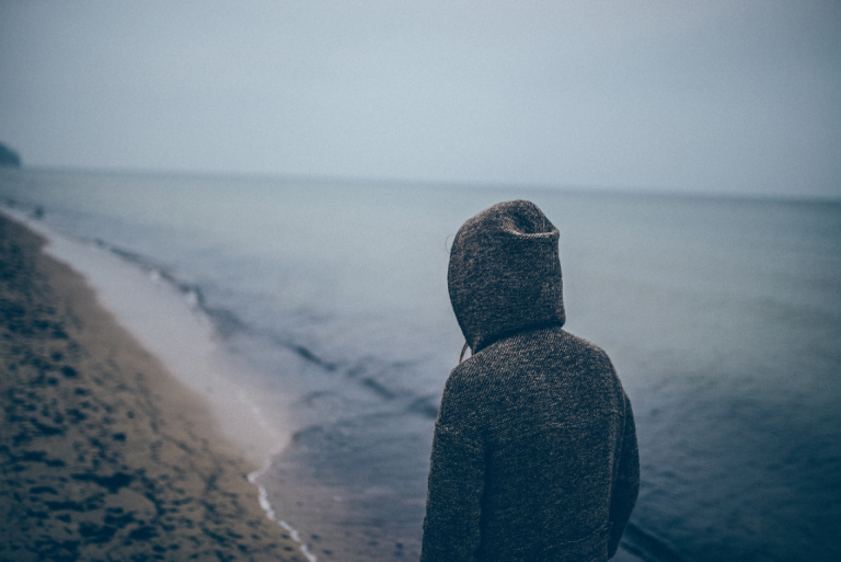 海辺を歩くフードを被った人