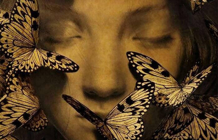 女性の顔に集まる蝶