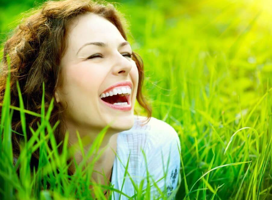 草むらで笑う女性